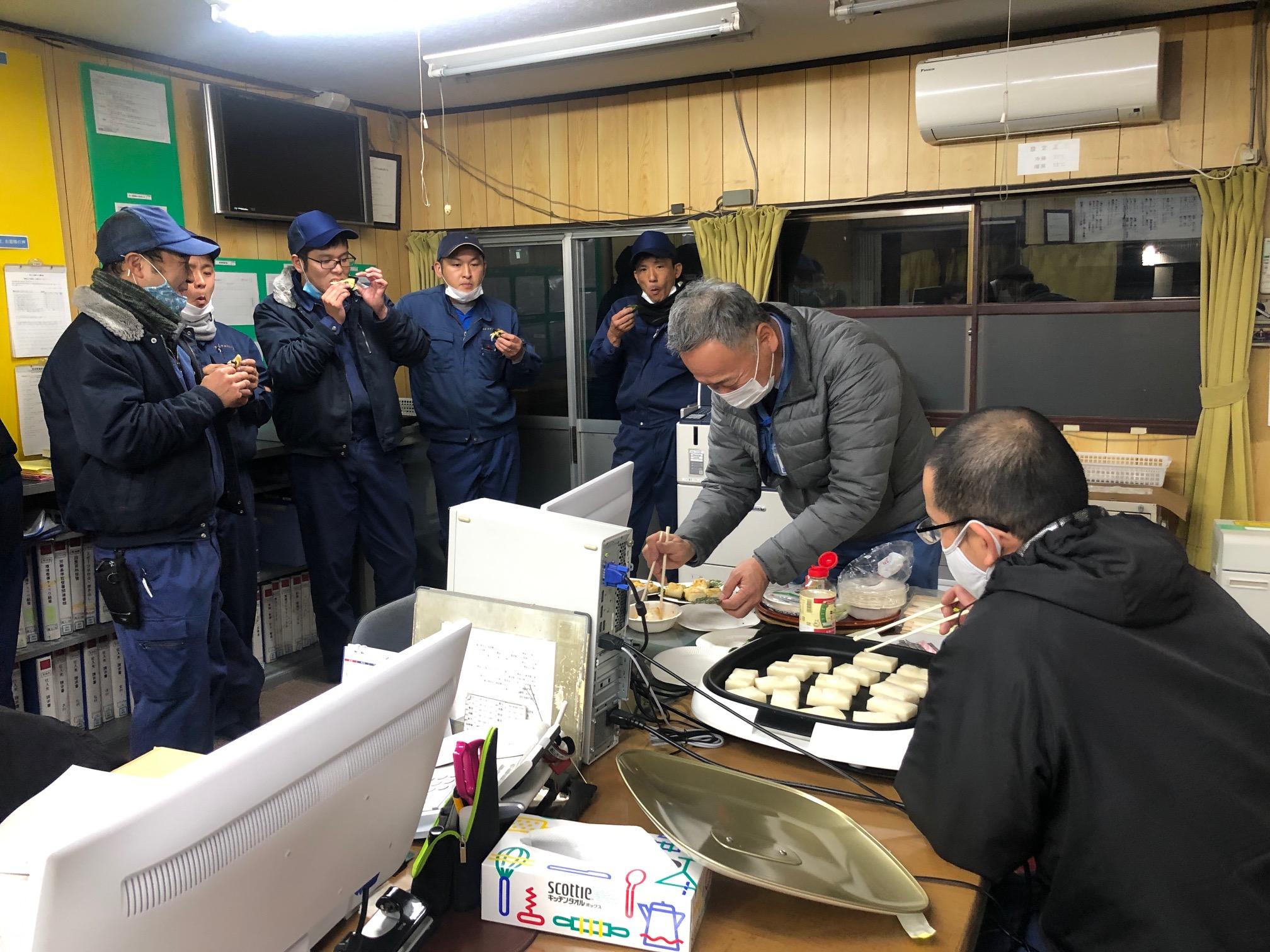 お餅を食べるサービスマンと、お餅を焼く社長と営業部長の写真